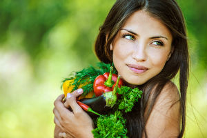 Vegan woman holding vegetables. A vegan is someone that avoids all meat, fish, poultry, and dairy products.