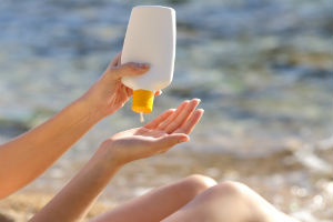 woman-putting-sunscreen-in-hand