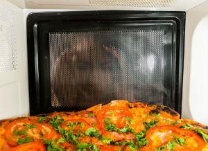 woman-peering-into-microwave