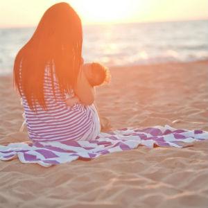 woman-on-beach-breasfeeding