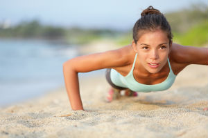 girl-doing-pushups-on-beach