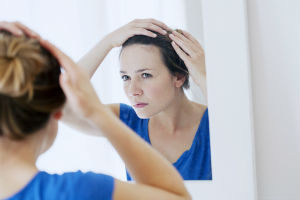 Woman looking in mirror wondering why her hair is thin