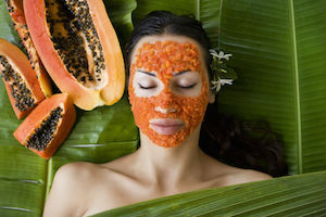 Woman with natural papaya skin care facial mask