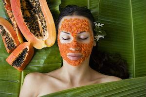 Woman with natural papaya skin care facial mask