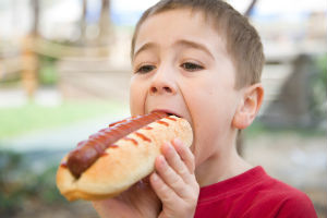 Picture of a child eating a hot dog depicting the risk of developing cancer by eating processed foods such as processed hot dog meat.