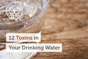 A glass of water sitting on a table. There can be many toxins in your drinking water that can negatively impact your health.