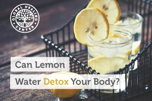 Two glasses of lemon water sitting on a table. Adding lemon water to your daily routine can help you detoxify your body.
