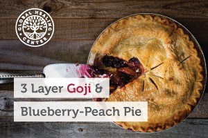 3 layer goji and blueberry peach pie on a wooden counter. This goji pie contains antioxidants which protect against free-radical damage.