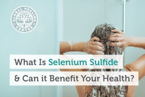 A woman is applying shampoo in the shower. Selenium sulfide is commonly found in cream, foam, shampoo, or in liquid form.
