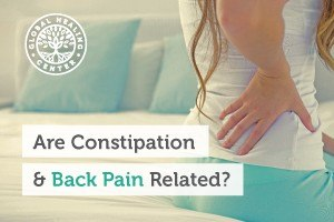 A woman holding her lower back. There are reports that harsh or minor constipation can cause back pain for individuals.