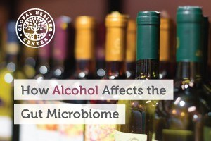 Several wine bottles on a shelf. Heavy alcohol consumption can lead to an imbalance of the gut microbiota and negatively impact health.