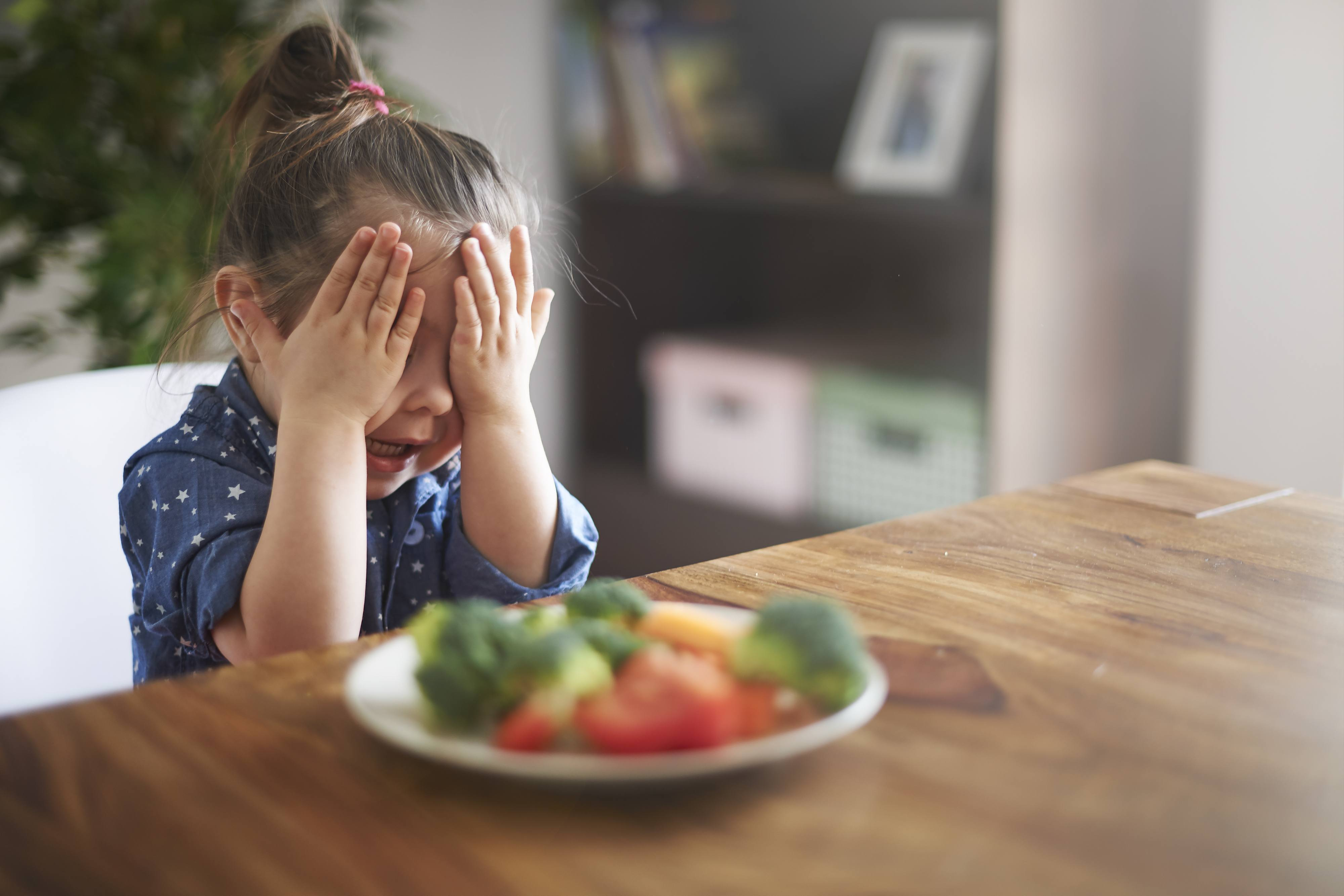 Forming dietary habits. A girl refuses to eat vegetables.