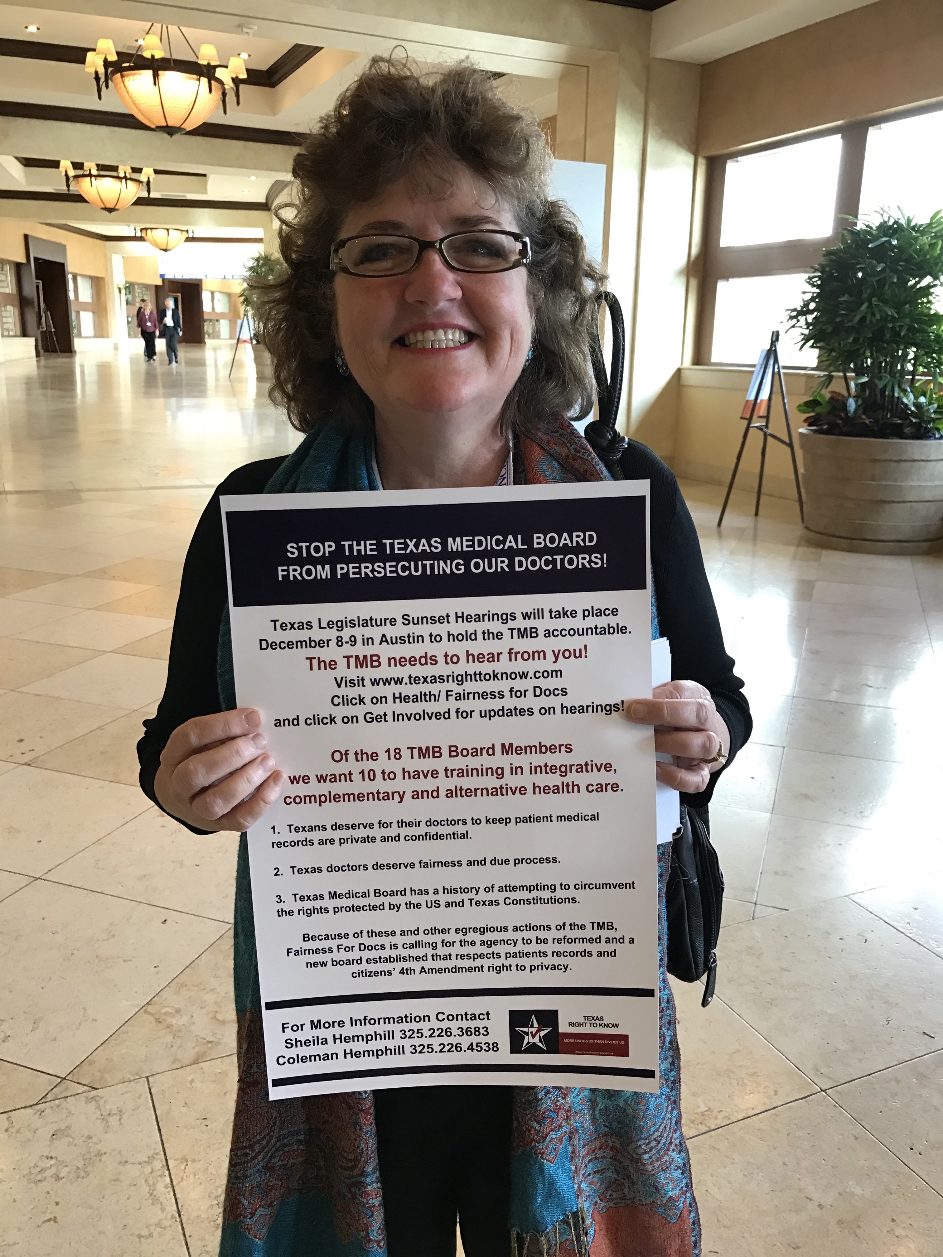 Program Director Shela Hemphill holds a 'Stop The Texas Medical Board From Persecuting Our Doctors' poster at the Truth About Cancer Symposium