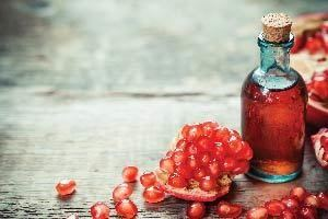A bottle of organic pomegranate oil with pomegranates seeds around it.