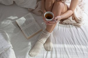 Woman relaxing in bed. A way to manage your stress.