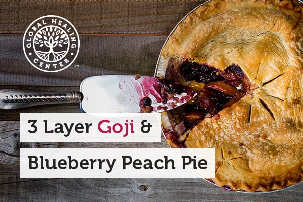 3 layer goji and blueberry peach pie on a wooden counter. This goji pie helps protect against free-radical damage.