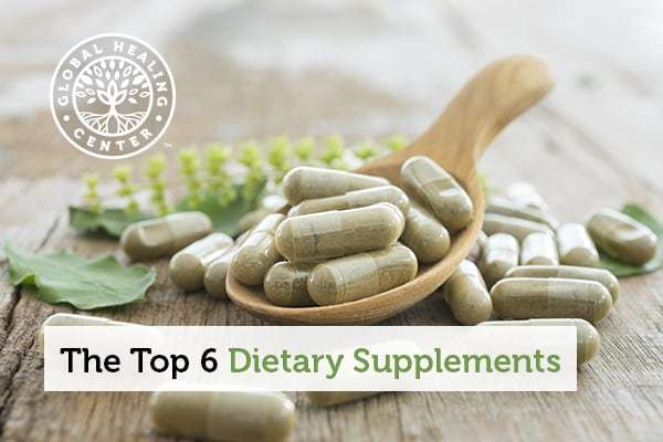 Dietary supplements on a wooden spoon.