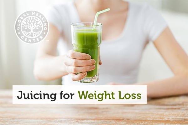 A person is holding a glass. Juicing with organic fruits and vegetables may help you lose weight.