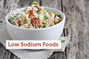 A bowl of low sodium foods including quinoa, tomatoes, and spinach.