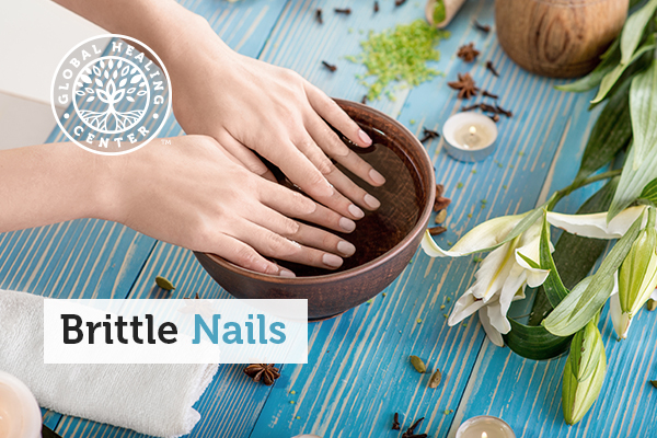 A woman soaking her nails in a homemade cuticle oil to strengthen nails. This is a natural remedy for brittle nails.
