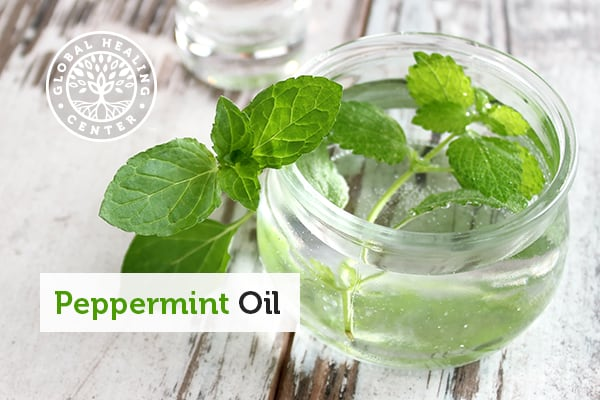 A bowl of peppermint leaves in a carrier oil.