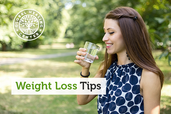 A woman drinking a glass of water. A effective weight loss tip is to drink 6-8 glasses of water daily.