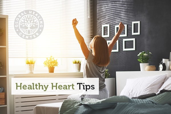 A woman waking up from a restful night's sleep. Adequate sleep is essential for heart health.