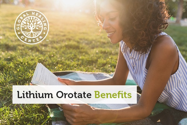 A woman relieving stress by reading in the park. Lithium orotate is another way to manage stress.