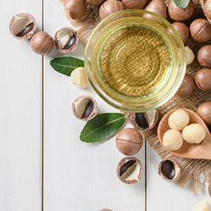 A bowl of macadamia oil and macadamia nuts. Macadamia nuts are one of the best sources of omega-7.