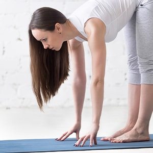 Woman stretching on yoga mat. Stretching is a natural home remedy that can help alleviate symptoms of restless leg syndrome.