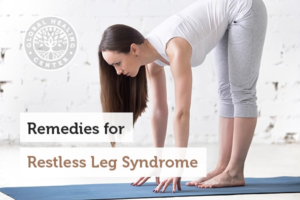 Woman stretching on yoga mat. Stretching is a home remedy for symptoms of restless leg syndrome.