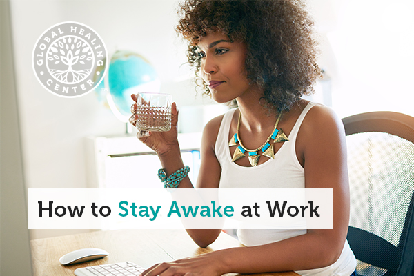 A woman drinking water while working. Maintaining hydrate is key for staying awake at work.