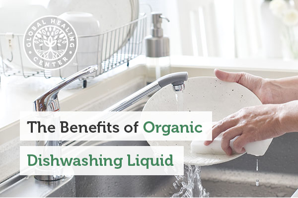 A person washing dishes with organic dishwashing soap.