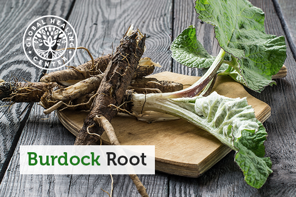 Burdock root and leaves on a cutting board.