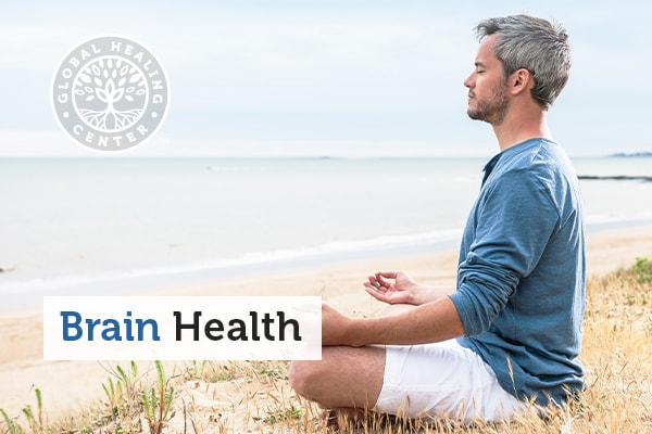 A man meditating on the beach which helps with brain health.