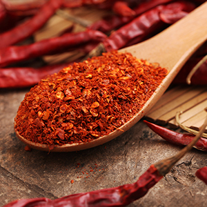 Ground cayenne pepper in a spoon with cayenne peppers in the background.