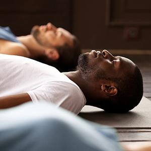 People on floor in deep meditation.