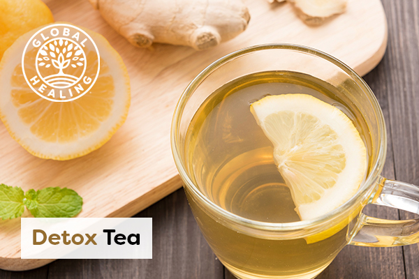 Tea with lemon in a glass cup over a wooden background with of natural ingredients.