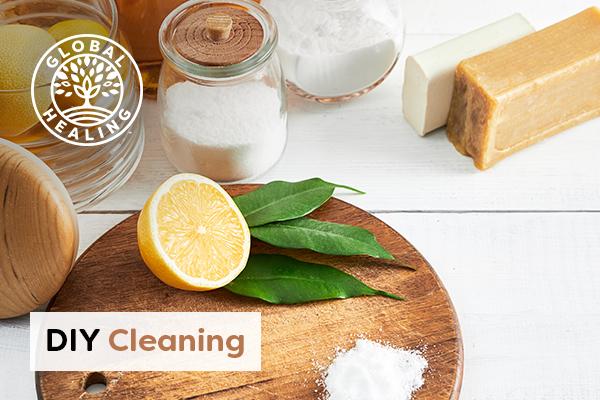 Half cut lemon on with a jar of baking soda on wooden cutting board