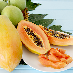 Papaya fruit cut in half with smaller pieces on a plate with green leaves in the background.
