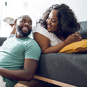 Man and woman on the couch, smiling at each other.