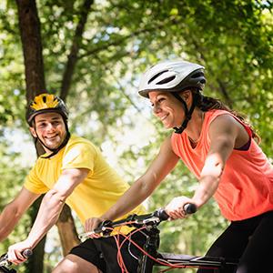 A couple on bike in green scenery.