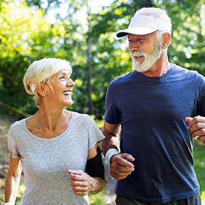 Man and woman jogging together in a green scenery.