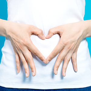 Woman's hands in shape of a heart over her belly.
