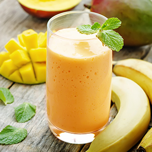 An orange smoothie in a glass over a wooden table with a mango and banana in the background.