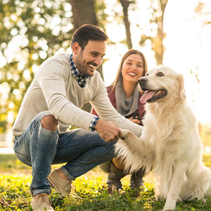 A man and woman with their dog in a natural green environment.
