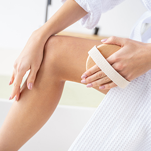 Woman using a dry brush on legs.