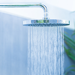 A shower head with running water.