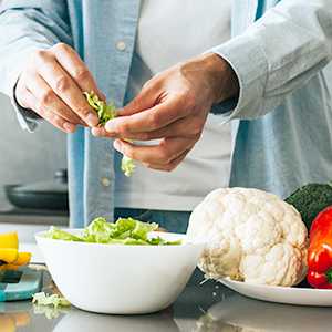 A person handling lettuce with bowls of vegetables over a kitchen counter.