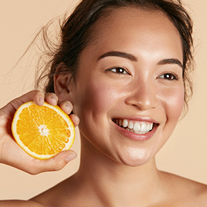 Smiling woman with orange in her hand.
